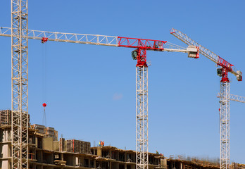 High-rise construction cranes and blue sky