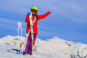 Girl standing with arms spreading wide open on the fresh powder snow at sunny day in mountains. Swiss Alps.