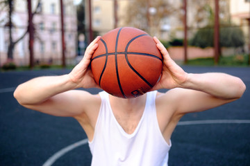 conceptual photo of basketball inspiration, man holding basketball ball instead of his head