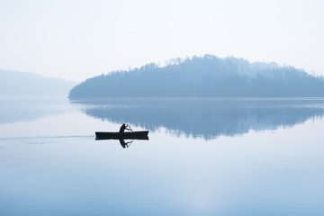 Foggy day. Autumn. Fog over the lake. A man is swimming in a boat.