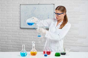 Scientist combines hot chemical substances, using chemical equipment : bottles and flasks. She works in the white lab and wears protective eyeglasses and uniform, that helps not to hurt herself.