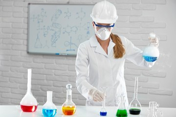 The scientist works with smoky chemical liquids in the lab. She uses special equipment made from glass . The chemist wears white protective uniform:chemical facemesk,gloves and eyeglasses.