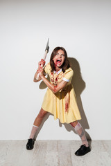 Full-length image of mad woman in dress ready to attack