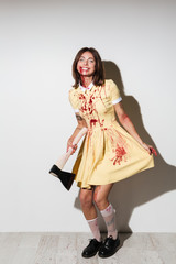 Full length image of happy zombie woman in dress