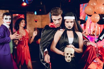 A guy in a vampire costume is standing in charge of a girl dressed as sexy nun. The girl is holding a skull in her hands