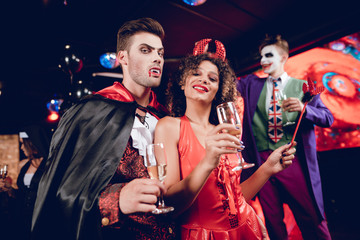A guy dressed as a vampire and a girl dressed as a demon posing with champagne glasses in their hands and have fun