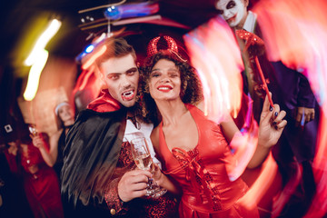 Long exposure. Motion blur. A guy dressed as a vampire and a girl dressed as a demon posing with champagne glasses.