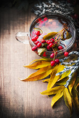 Cup of autumn tea with healthy healing berries and fall leaves, top view