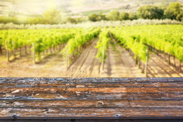 Foto auf AluDibond Weinberg Empty wooden table top, sunny vineyard background, ready to use for display or montage of your products