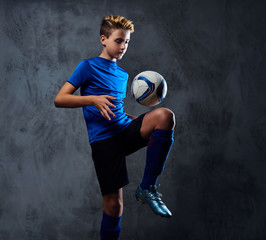 Teenager soccer player dressed in a blue uniform plays with a ball.