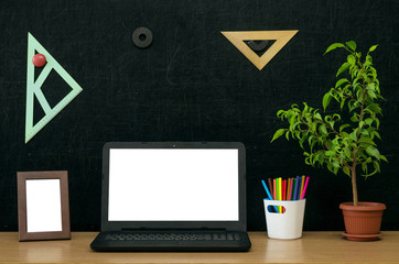 Teacher or student desk table. Education background. Education concept. Laptop with blank screen, green plant tree, book (copybook), colour pencils, photo frame on blackboard.