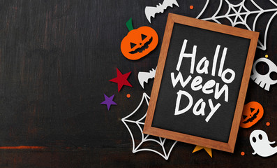 halloween background. pumpkin, bats and spider cut of paper and wooden frame. space for text