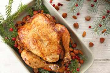 Baking dish with roasted turkey, fir tree branches and nuts on table