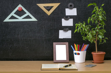 Teacher or student desk table. Education background. Education concept. Plant in pot, color pencils, note paper, copybook with pen and photo frame on blackboard (chalkboard) background.
