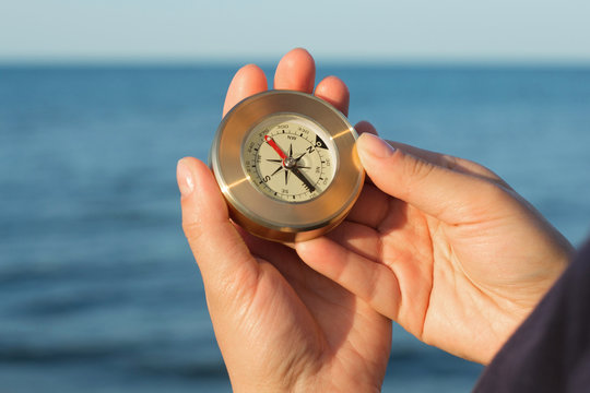 Hands holds a little compass indicating the direction on the background of the sea