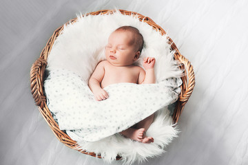 Sleeping newborn baby in a wrap on white blanket.