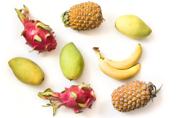 Isolated tropical fruits. Pineapple, banana, pitaya fruit and mango isolated on white background. Top view.