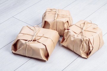 Gifts packed in craft paper package tied a rope on a white oak desk floor.