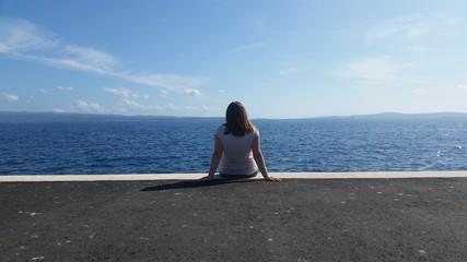Frau sitzt im Hafen und genießt die Aussicht