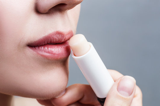 Beautiful woman applying hygienic lip balm.