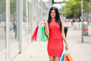 Beautiful woman outdoors with plenty of shopping bags