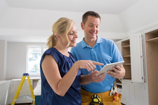 Woman With Carpenter Looking At Plans For New Kitchen On digital Tablet