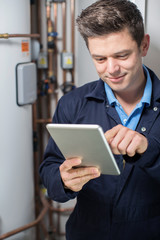 Male Plumber Working On Central Heating Boiler Using Digital Tablet