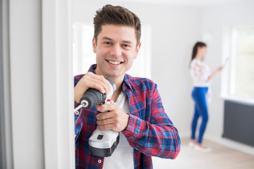 Man Using Electric Drill As Couple Renovate Property Together