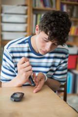 Teenage Boy Testing Blood Sugar Level At Home