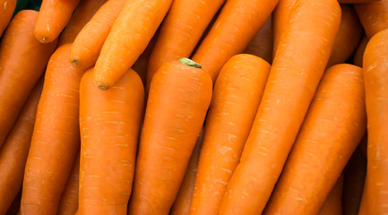 Close up a fresh carrots for background. The Carrot is root vegetable, usually orange in colour, though purple,  yellow cultivars exist.