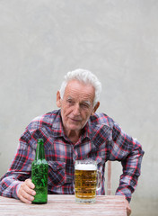 Senior man with beer bottle and mug