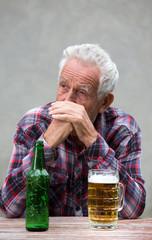 Senior man with beer bottle and mug