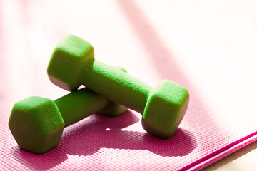 Two green dumbbells on pink yoga mat