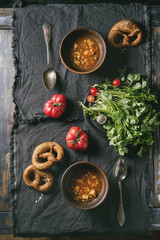 Clay bowls with vegetarian hot carrot tomato pea potato soup, served with fresh coriander, pretzels bread and tomatoes on textile napkin over old wooden plank table. Flat lay