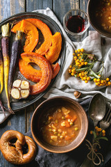 Fall holiday table decoration setting with bowls of hot carrot potato soup, baking pumpkin, carrot, garlic, pretzels bread, red wine, orange berries. Flat lay over wooden table