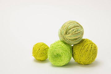 Green thread for knitting in tangles and needles with flowers on a white background