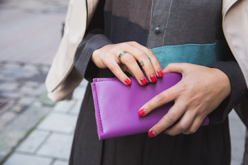 Woman's hands with purple lether wallet. Street fashion element