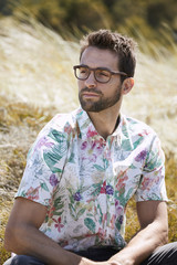 Glasses and stubble guy in floral shirt, looking away