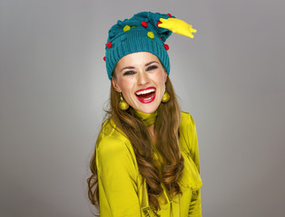 cheerful young woman in funny Christmas hat isolated on grey