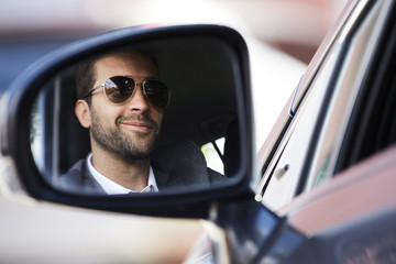 Smiling stubble guy in rear view mirror of car