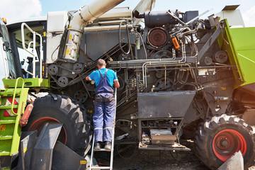 Combine machine service, mechanic repairing motor outdoors