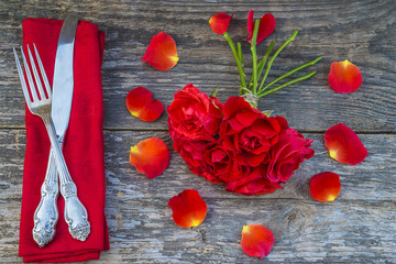 romantic dinner concept/vintage cutlery on red napkin and bouquet of red rose flowers on rustic background