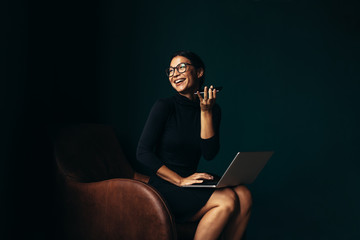 Smiling woman sitting in chair with laptop and talking on smartphone