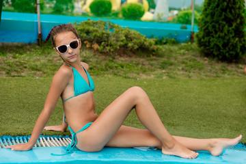 Beautiful girl in a swimsuit swims in the pool