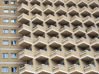 large residenetial highrise building with angular rows of balconies and vertical lines of windows