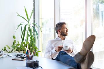 Wall Mural - Businessman in his office, having a break, drinking coffee.