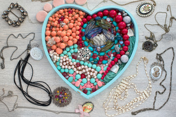 A set of jewelry for women on a wooden tray in the shape of a heart.