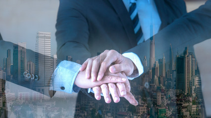 Double exposure of Businessmen put hands together in the concept of team work and coorperation overlay with the city landscape.