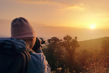 Male backpacker taking photograph at sunset in morning. Travel to Doi Inthanon, Chiangmai, Thailand.