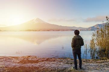 Asian man traveler looking sunrise and mount fuji reflect on water in morning at kawaguchiko lake japan